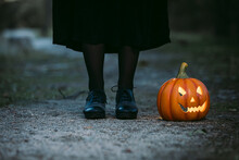 Crop Woman Standing With Jack O Lantern In Woods On Halloween