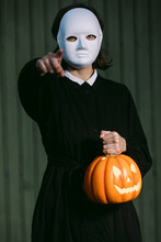 Unrecognizable Woman With Pumpkin Lantern And In Halloween Mask In Street