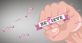 Composition of pink ribbon logo and believe text with fist
