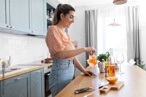 Fototapeta culinary, drinks and people concept - happy smiling young woman making orange co