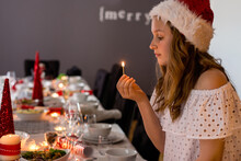 Lighting Candles On The Christmas Dining Table