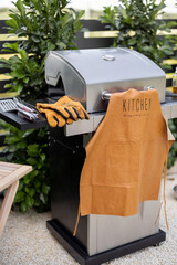 Modern gas grill with leather apron and gloves stands at backyard