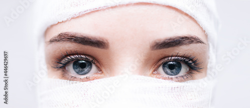 Photographie close-up of a girl's face in medical bandages after surgery on a white backgroun