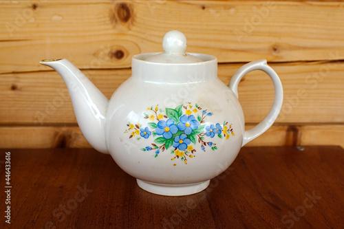Obraz na plátně an earthenware teapot on a table against a wooden wall