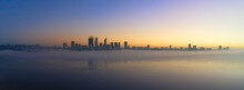 Panoramic Shot Of Perth Skyline At Dawn With Misty Atmosphere And Some Buildings Reflected On Water