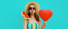 Portrait Of Beautiful Young Woman With Slice Of Fresh Watermelon And Big Red Heart Shaped Balloon Blowing Her Lips Wearing A Summer Straw Hat, Sunglasses On Blue Background