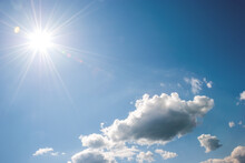Heap, White Clouds, Sun With Long Rays And Glare In The Blue Sky. Sky Landscape