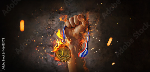woman hand raised, holding gold medal in the fire. award and victory concept