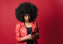 Black Woman With Pouting Lips Browsing Smartphone In Studio