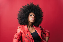 Black Woman With Curly Hair Looking At Camera On Red Background