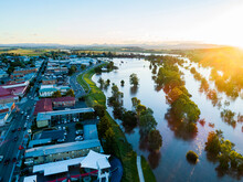 Aerial View Of River Flooding Beside Town With Water Rising During Natural Disaster
