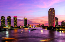 Bangkok Thailand Cityscape And Chao Phra Ya Riverfront View On The Sunset Period With Beautiful Twilight And Motion Blurred Of Boat. For Use As Asian, Thailand Night City Scape Background Material.