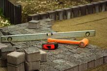 Budowa Chodnika - Młotek, Poziomica I Metrówka . Construction Of The Pavement - A Hammer, A Spirit Level And A Ruler.