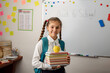Cute girl with a backpack, stack of books and an apple on top standing in classroom of conventional school. Concept of education, back to school after summer holidays