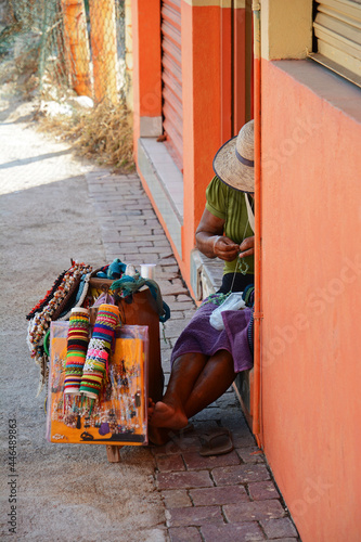 Slika na platnu Mexican woman sitting on sidewalk in alcove making crafts for tourists