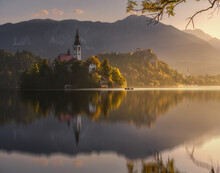 Scenic View Of Lake And Church In Mountains On Sunny Day