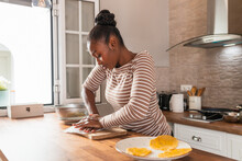 Black Woman Preparing Tostones At Table In Kitchen