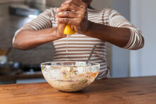 Crop Black Woman Squeezing Lemon Above Food In Bowl