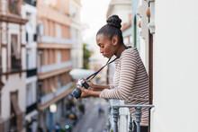 Black Photographer With Digital Photo Camera On Balcony