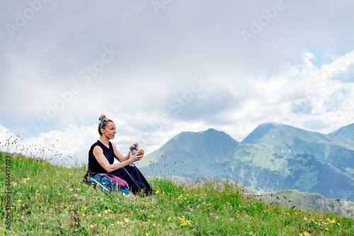 Fototapeta A blonde tourist sits on the grass, eats and drinks water, rests in the beautiful Polish mountains