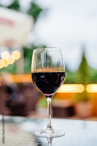 Fototapeta A glass of red wine stands on a table in a restaurant.