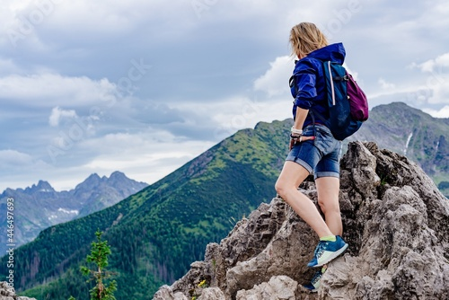 Fototapeta The rear view of the blonde traveler is standing on a rock and admiring the beautiful mountain views