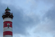 Red And White Striped Lighthouse On The Background Of A Stormy Sky. Free Copy Space For Design Or Text
