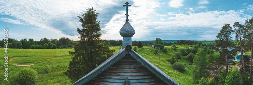Foto Old wooden church among the overgrown field