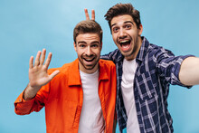 Cool Guys In Stylish Outfits Have Fun And Widely Smile On Blue Background. Guy In Checkered Shirt Makes Bunny Ears To His Friend.