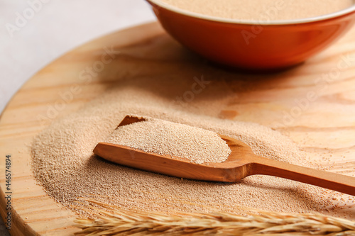 Fotografie, Obraz Scoop with active dry yeast on wooden board, closeup