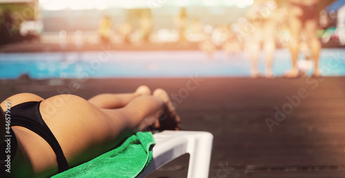 Fotografia Banner young woman relax in bikini lies on sunbed with tanned skin, background s