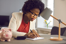 Positive Millennial African American Business Woman Carefully Writes Notes Sitting Near Calculator And Piggy Bank. Woman Checks The Bills, Keeps Track Of Expenses And Plans The Budget.