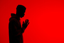 Anonymous Black Man Praying With Clasped Hands On Red Background