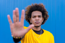Black Man Showing Stop Gesture Against Blue Wall