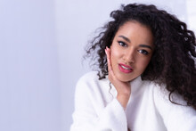 Close Up Portrait Of Positive Charming Mixed Race Young Girl With Healthy Smooth Skin And Perfect Modern Makeup Looking At Camera, Attractive Curly Biracial Female In White Sweater Posing In Studio.