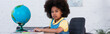 African american girl looking at camera near stationery and globe on table, banner