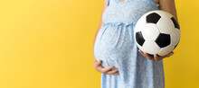 Motherhood, Femininity, Football, Sport, Dairy, Hot Summer. Banner Pregnant Young Pretty Woman In Floral Blue Dress Holds Soccer White And Black Leather Classic Ball Rubs Tummy On Yellow Background