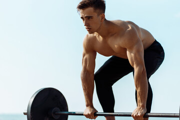 Fototapeta na wymiar Young muscular man doing chest workout with dumbbells with big weights, on the beach on, a man with big muscles