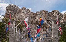 Black Hills, Keystone, SD, USA - May 31, 2008: Mount Rushmore. Colorful State Flags In Front Of The Famous Sculpture Of 4 Presidents. Gray Granite Under Blue Cloudscape.