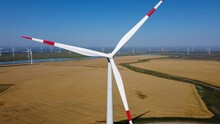 Wind Energy Working In The Field. Large Rotating Blades. A Source Of Renewable Energy. Blue Sky. The Drone Is Moving Away In A Straight Line