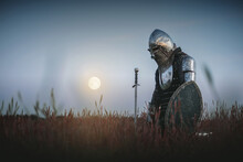 The Tired Knight In The Plate Armor Kneels Among The Battlefield With A Sword In The Moon Light. Lost Battle. Defeat Concept.