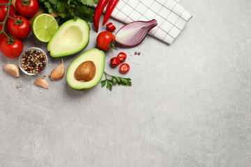 Fresh guacamole ingredients on light grey table, flat lay. Space for text