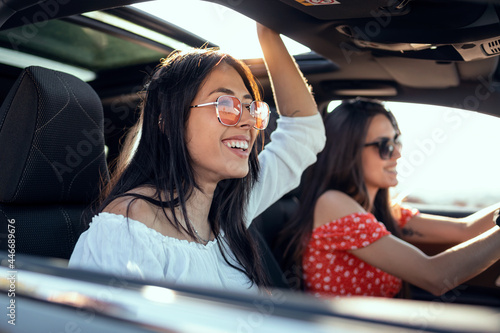 Fotografie, Tablou Pretty young women singing while driving a car on road trip on beautiful summer day