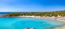 Crystal Clear Turquoise Water In A Glystra Beach. Cane Umbrellas And Sunbeds On An Beach Resort - Vacation Concept On Greece Islands In Aegean And Mediterranean Sea. Near Lindos At East Rhodes. Greece
