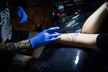 Cropped Shot Of Tattooing Process On Hand In Salon. A Professional Tattoo Artist Introduces Ink Into The Skin Using A Needle From A Tattoo Machine.Professional Tattooist Working In Studio.