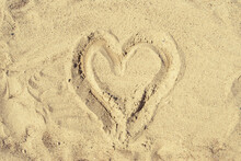 A Heart Drawn In The Sand. Texture Of River And Sea Sand, Background.