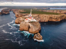 Aerial View Of Farol Do Cabo De Sao Vicente, A Beautiful Lighthouse On The Cliff At Sunset Facing The Ocean, Sagres, Algarve Region, Portugal.