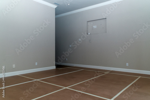Stampa su Tela A big empty neutral colored room room with tape on the floor forming a grid and