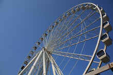 Low Angle Shot Of A Ferris Wheel Ride On A Blue Sky Background
