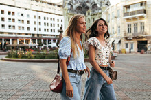 Blonde And Brunette Women In Stylish Loose Jeans And Floral Trendy Blouses Walk And Talk In Good Mood Outside. Portrait Of Attractive Girlfriends.